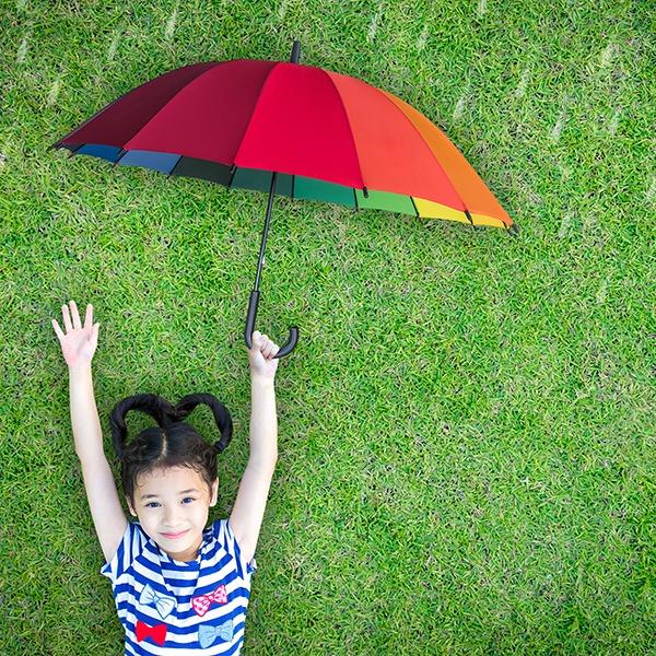 Mädchen mit buntem Regenschirm liegt auf der Wiese. Sie ist vor den fallenden Regentropfen geschützt.