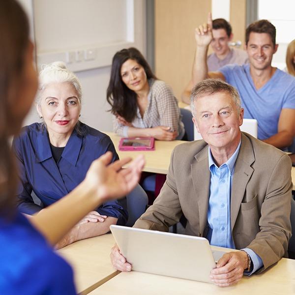 Erwachsene sitzen in Bankreihen, haben ihren Laptop oder Tablet bei sich und hören einer Vortragenden zu