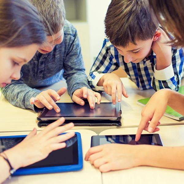 Das Bild zeigt Kinder, die in ihre Tablets vertieft sind.