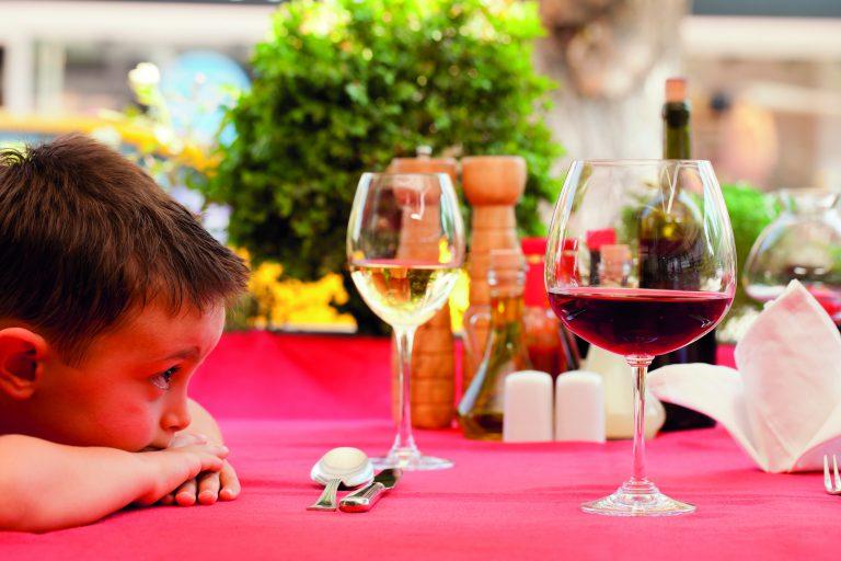 Kind schaut interessiert auf eine volles Weinglas.
