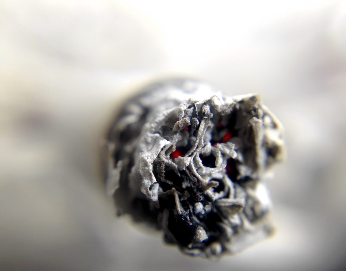 Nahaufnahme der Spitze einer glühenden Zigarette.