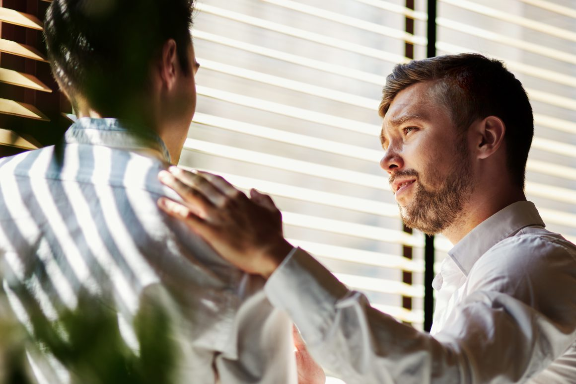 ein Geschäftsmann spricht empathisch mit einem Kollegen